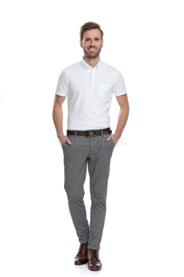 Счастливое уверенное случайное положение человека с руками в карманах стоковая фотография rf