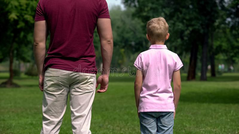 Сын и отец стоя совместно, смотрящ в будущем, один взгляд семьи родителя задний стоковая фотография rf