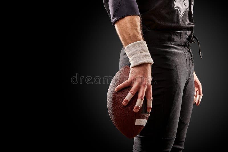 Средний раздел американского футболиста с шариком против черноты, космоса экземпляра, взгляда со стороны стоковые изображения