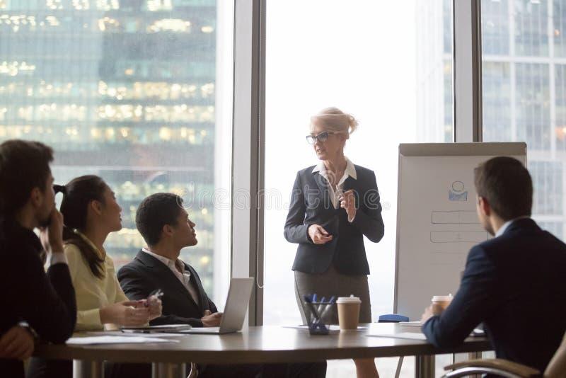 Средн-достигшая возраста исполнительная власть дает лекцию по представления для разнообразной корпоративной команды стоковая фотография