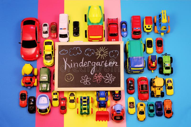 Ð¡halkboard with the inscription: Kindergarten, surrounded by colored cars on multicolored background. Top view royalty free stock photography