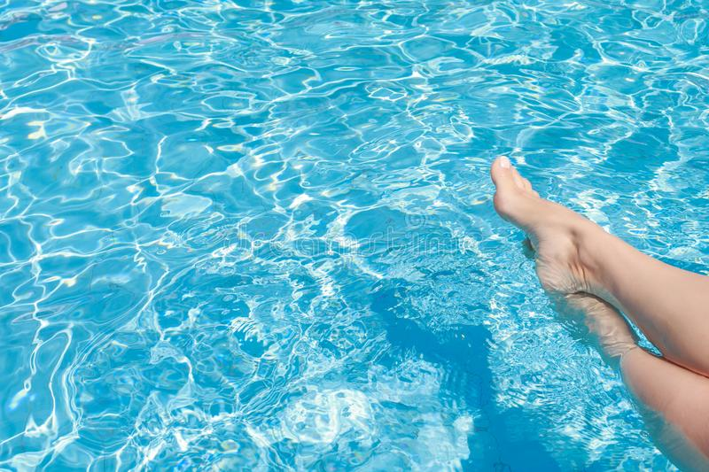 Ð¡harming women`s legs are lowered into the clear water of the turquoise pool.  royalty free stock photo