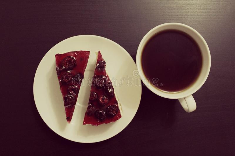 Ð¡heesecake and tea. Cherry cheesecake with fragrant black tea. A white saucer and a black table stock photos