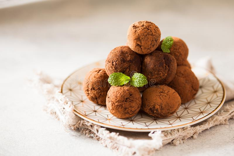 Ð¡hocolate truffles with cocoa powder on white dessert plate royalty free stock photography