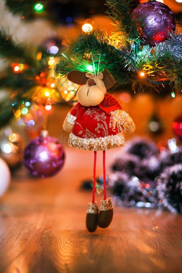 Ð¡hristmas deer stuffed toy on Christmas tree. Christmas tree and ball on bokeh background. Shallow depth of feild stock photos