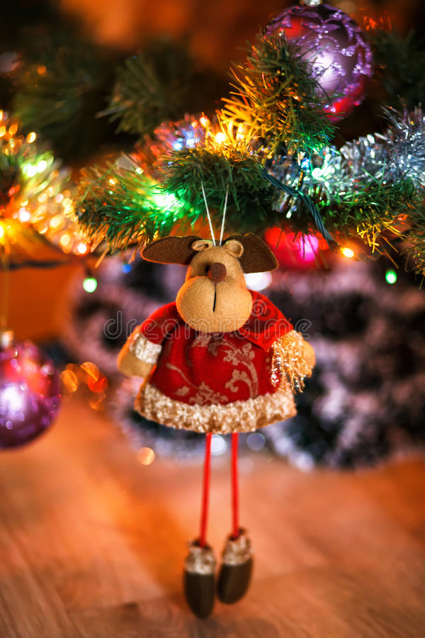Ð¡hristmas deer stuffed toy on Christmas tree. Christmas tree and ball on bokeh background. Shallow depth of feild. Focused on face of toy royalty free stock photos