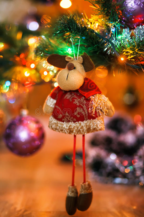 Ð¡hristmas deer stuffed toy on Christmas tree. Christmas tree and ball on bokeh background. Shallow depth of feild. Focused on face of toy stock photos