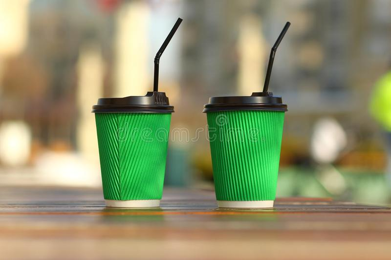 Ð¡loseup of green paper coffee cups on the outdoor wooden surface, place for logo, straws looking the same direction. Ð¡loseup of green paper coffee cups on stock image