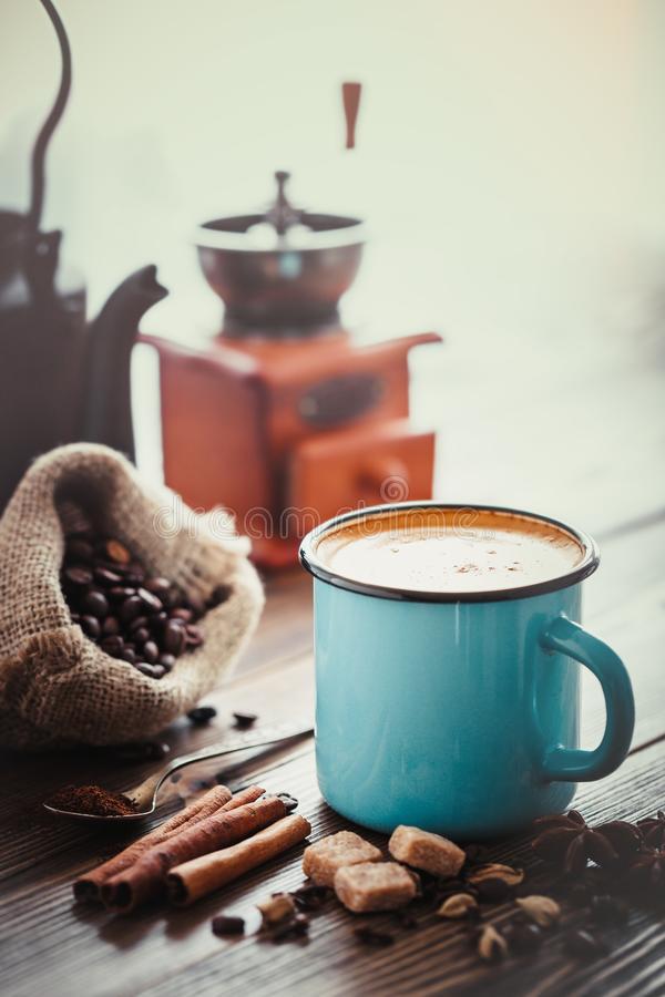 Ð¡offee in blue mug, sugar, coffee beans, spices and coffee mill on background. stock photo