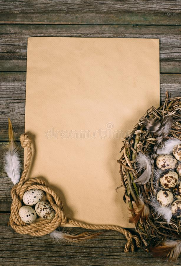 Ð¡oil of rope and nest with quail eggs on sheet of paper for text on old wood board. Vintage Easter or hunt mock up royalty free stock photo