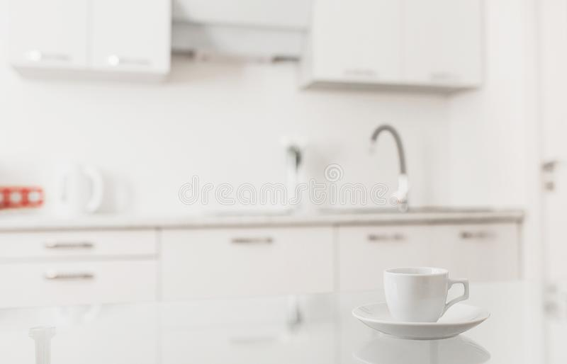 Ð¡ontemporary kitchen table with white tea mug. Minimal concept apartment. Coffee cup on glass table against background of kitchen. Modern kitchen furniture stock photo