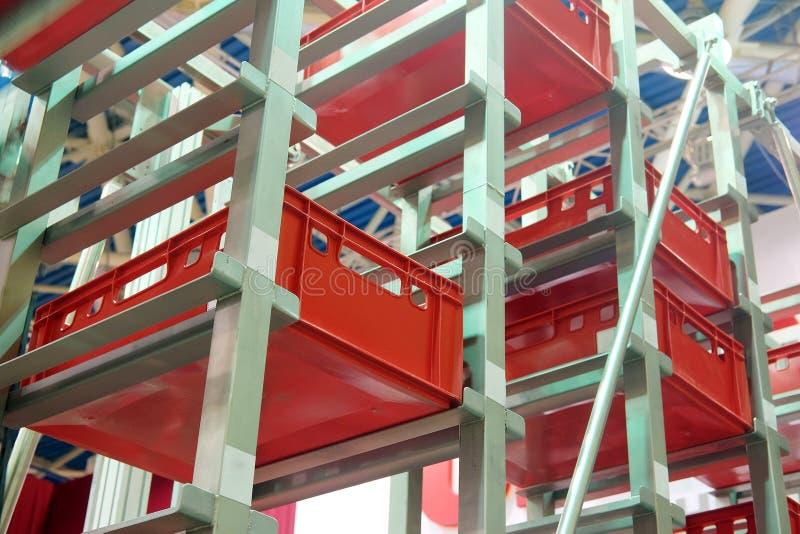 Ð¡onveyor for storage of plastic boxes stock image