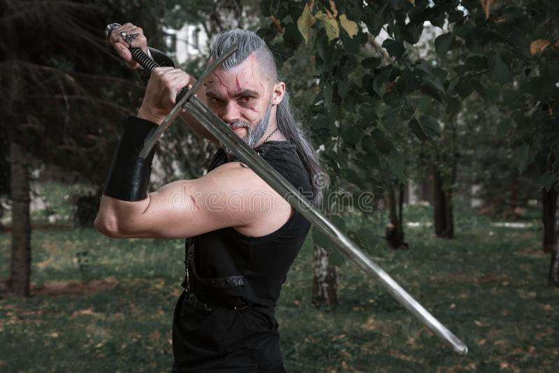 сosplay, dressed like a hero Geralt of Rivia from the game the Witcher, a fantastic warrior with a sword in his hands stock images