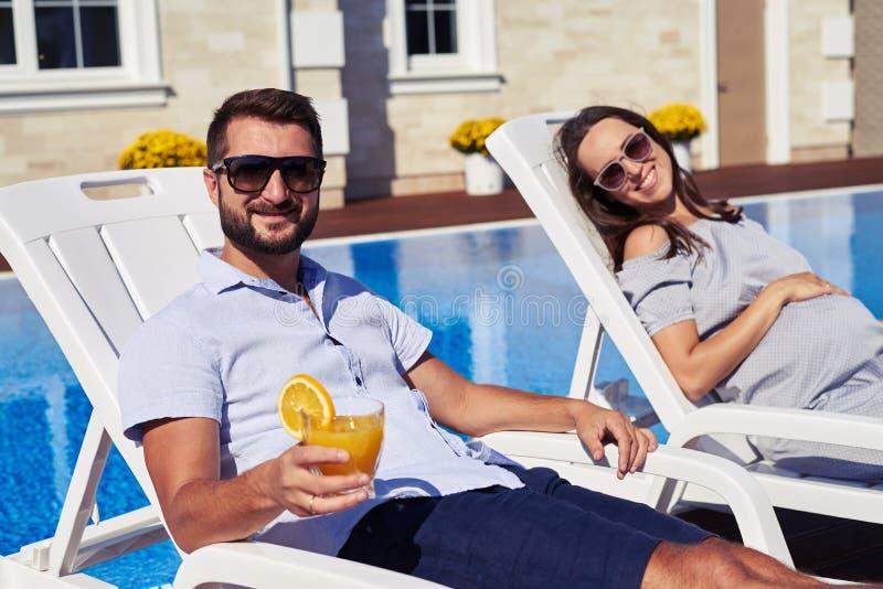 Ð¡ouple enjoying sun in modern residence near pool royalty free stock photo
