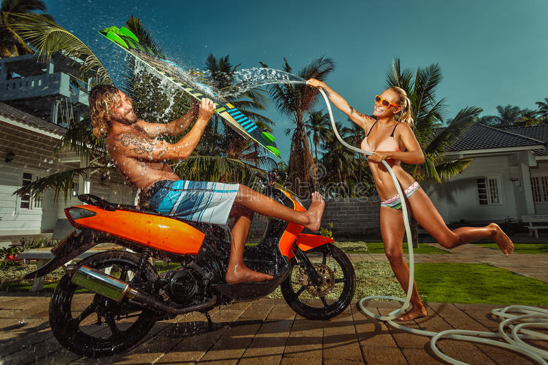 Ð¡ouple having fun with garden hose splashing summer rain royalty free stock images