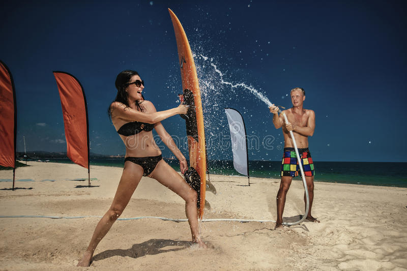Ð¡ouple having fun with hose splashing summer rain royalty free stock image