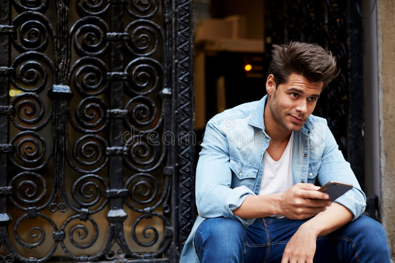 Ð¡ropped shot of a fashionable man using his mobile phone in urban setting stock images