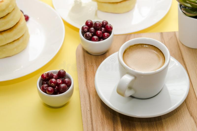 Ð¡up of coffee and berries on yellow background. Syrniki. Russian food. Copy space. stock photography