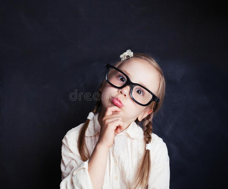 Сurious child thinking. Funny little girl in glasses stock photography