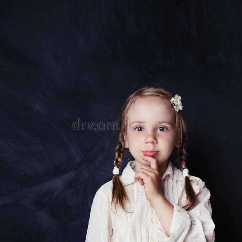 Сurious child thinking. Little girl on chalk board background stock images