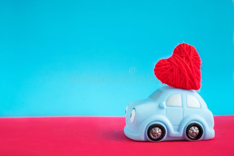 Ð¡ute blue toy with red thread heart for Valentine`s day against. Blue and red background. Love, romance, Valentines day concept. Selective focus royalty free stock photo