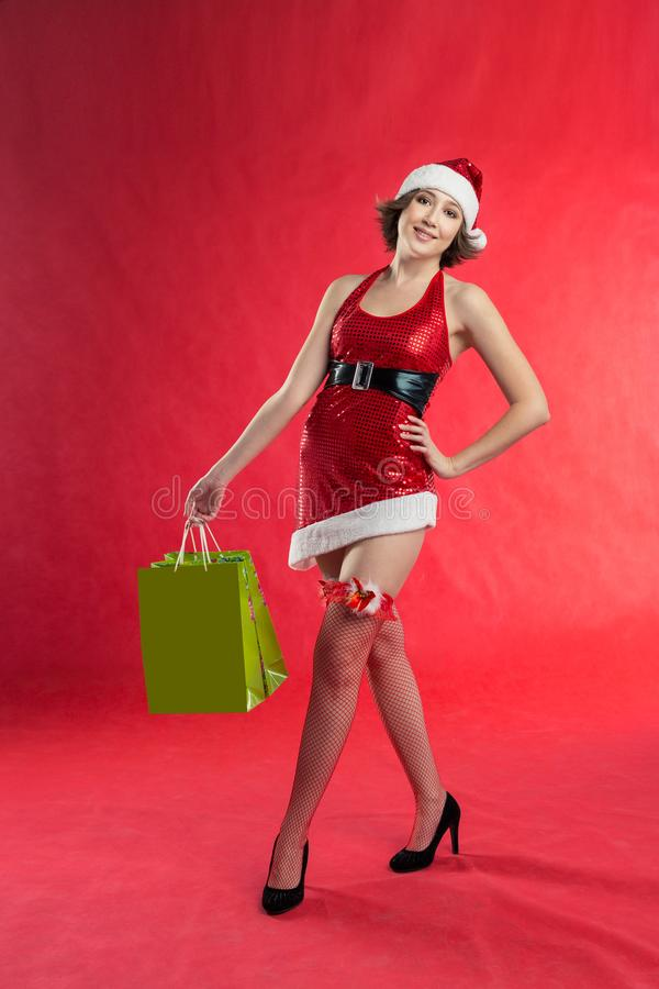 Ð¡ute girl dressed as Santa Claus and stockings holds shopping bags, holds hand at the waist stock images