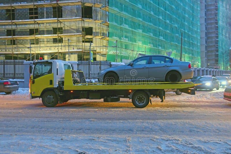 Эвакуатор транспортируя автомобиль на улице города стоковые фото