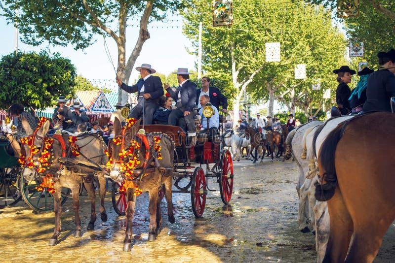 Экипажи и всадники лошади вычерченные на ярмарке в апреле, Севилье Справедлив Feria de Севилья стоковые фотографии rf