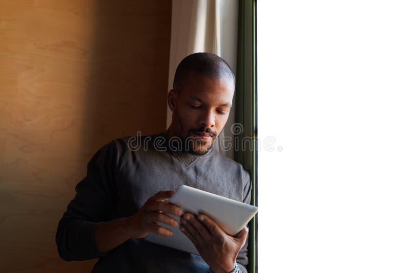 Элегантный африканский чернокожий человек используя планшет дома живя комната стоковые изображения rf