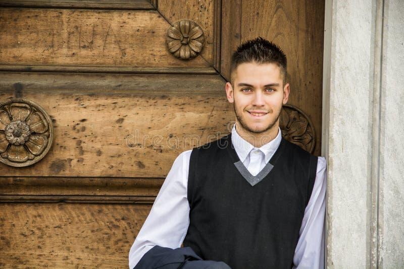 Элегантный молодой человек полагаясь против деревянной двери стоковые фото