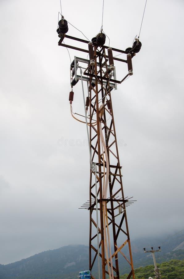 Электрическая башня в горах, положенных в кожух в туман стоковая фотография rf