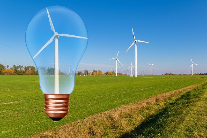 Электрическая лампочка с ветротурбиной внутрь на предпосылке голубого неба и зеленом поле с турбинами стоковые фотографии rf