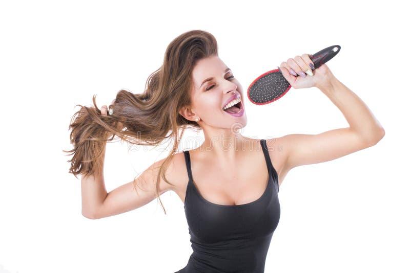 Эмоциональная белокурая женщина поя с гребнем волос, изолированным на белизне Концепция ухода за волосами стоковая фотография rf