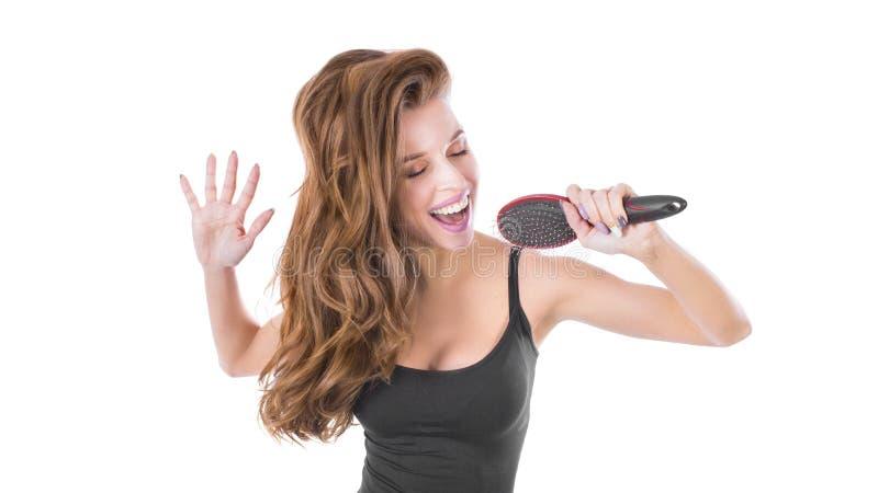 Эмоциональная белокурая женщина поя с гребнем волос, изолированным на белизне Концепция ухода за волосами стоковое фото