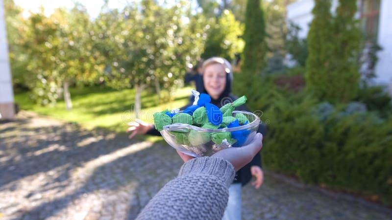 Эмоциональный мальчик бежать для того чтобы покрыть полное конфет, фокус-или-обрабатывающ на хеллоуине стоковое фото rf