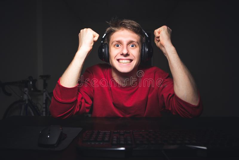 Эмоциональный gamer сидит дом в комнате вечером и видеоиграх игр стоковое фото