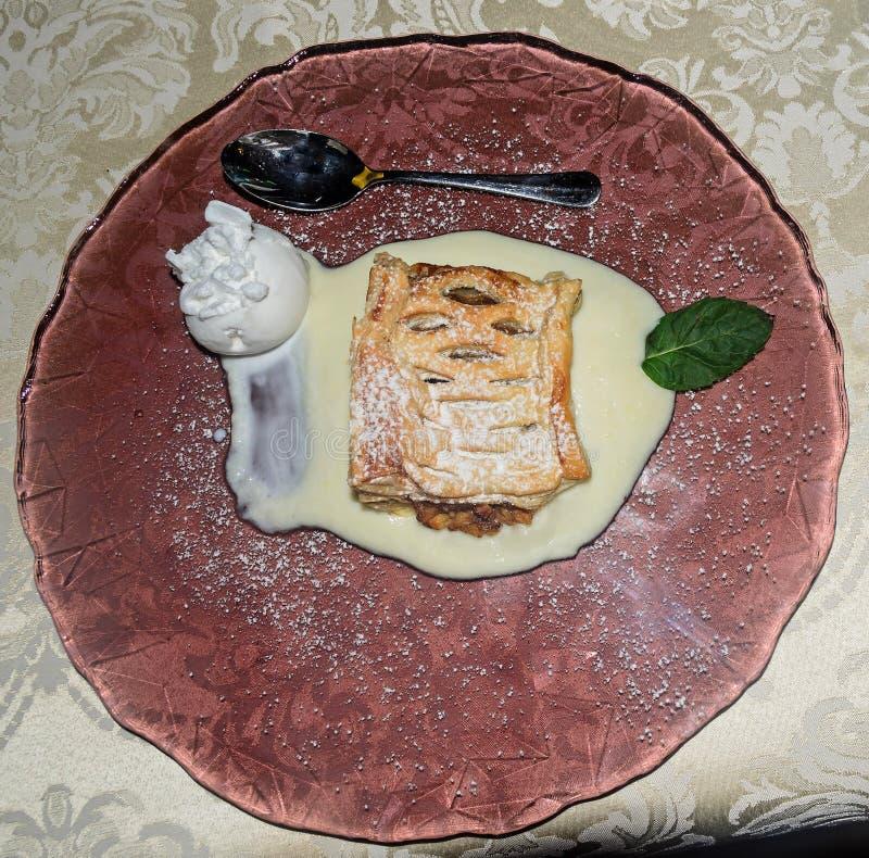 Яблочный пирог с мороженым на прозрачной коричневой плите, серебряной ложке стоковое изображение