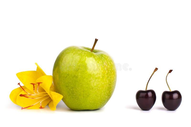 2 ягоды вишни и одно большого зеленого яблоко на белой конце изолированном предпосылкой вверх по макросу стоковая фотография rf