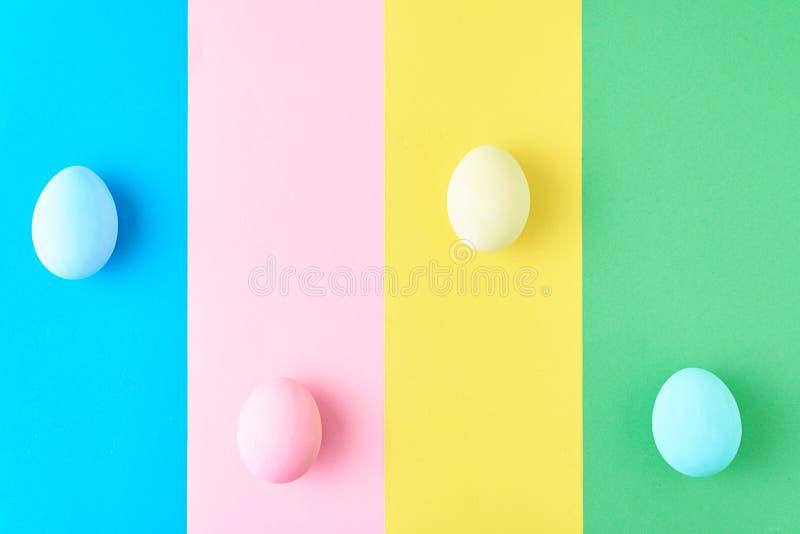 Яйца на покрашенной striped предпосылке, концепция минимализма стоковое изображение