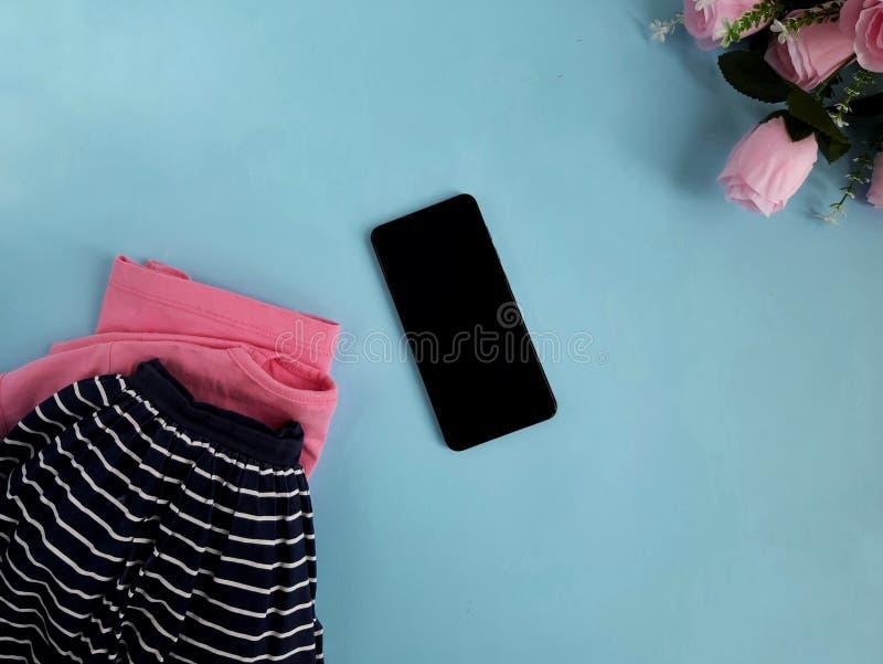 Яркая одежда цвета, подняла футболка, юбка белья военно-морского флота, телефон, цветки на голубой предпосылке стоковая фотография rf