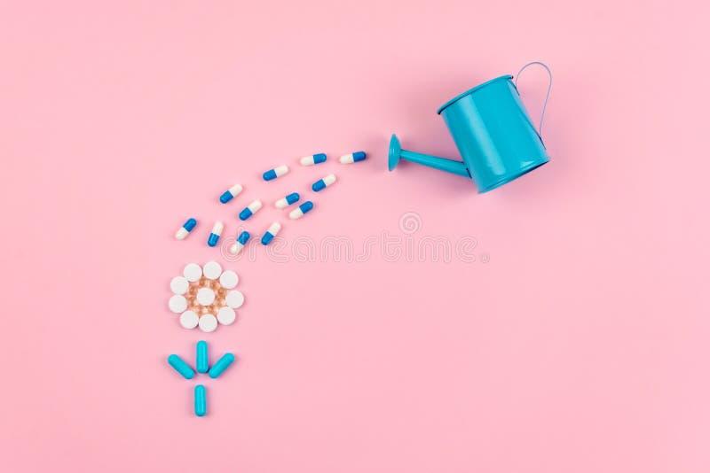 Яркие голубые и белые таблетки и планшеты в форме цветка и консервная банка сада моча на розовой предпосылке Медицины, лекарства, стоковая фотография