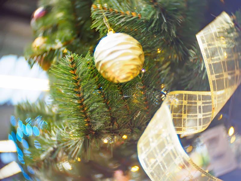 Яркий и красиво украшенный с рождественской елкой игрушек против сияющей загоренной нежности сфокусировал предпосылку стоковые изображения