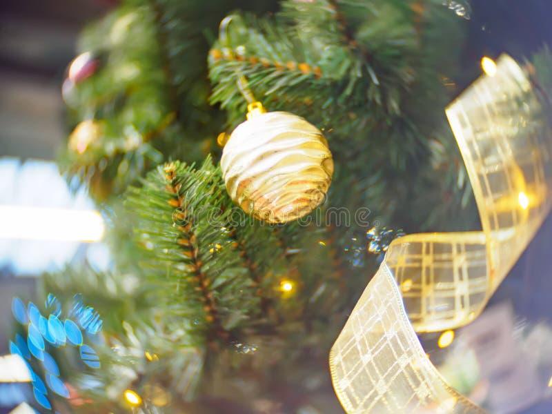 Яркий и красиво украшенный с рождественской елкой игрушек против сияющей загоренной нежности сфокусировал предпосылку стоковые фото
