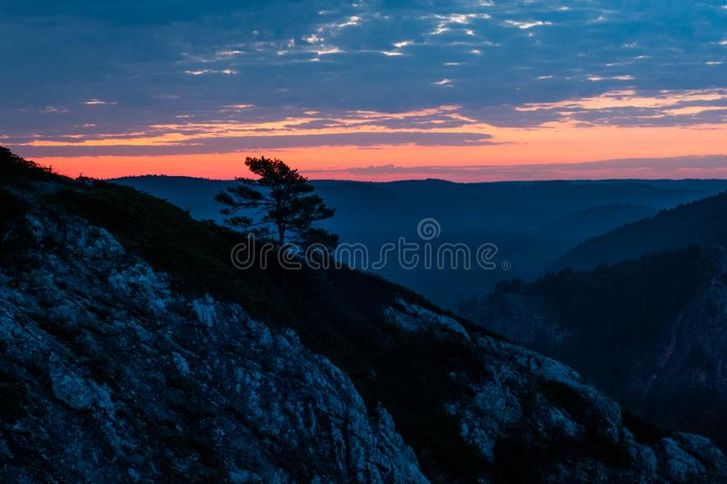 Яркий красный рассвет в горах в ветреном, пасмурном утре, солнце поднимает от горизонта стоковое фото