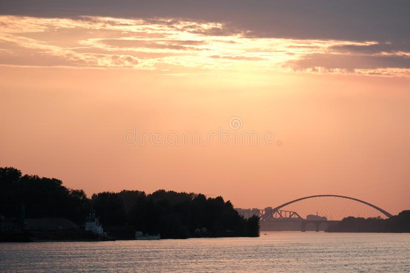 Ярко-красный закат на реке. Вдали виден мост. Вечерний закат. stock photo