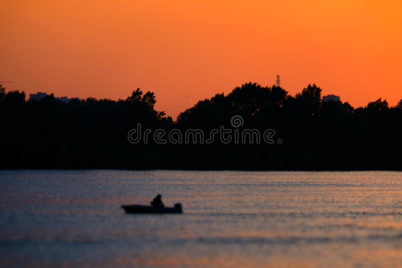 Ярко-красный закат на реке. Плывет лодка по воде. stock images