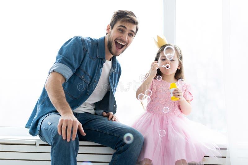 Я тебя люблю, папа! Красивый молодой человек дома с его маленькой девочкой имеет потеху и дуя пузыри мыла Счастливое ` s отца стоковые фотографии rf