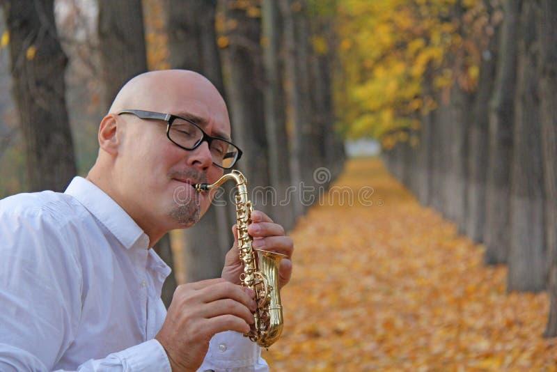 юмористика Мужской саксофонист в белой рубашке играя саксофон на предпосылке ландшафта осени Романтичный саксофон стоковые изображения