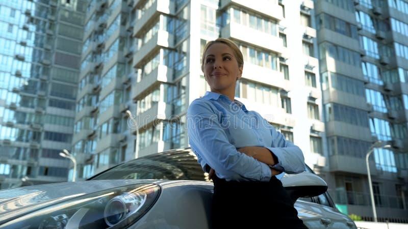 Уверенная дама в положении делового костюма полагаясь на новом автомобиле, успехе и богатстве стоковое изображение