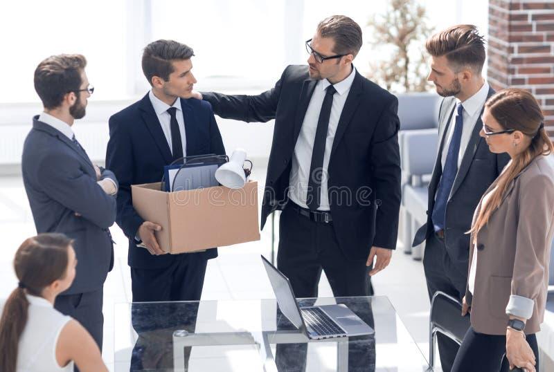 Уволенный работник с личными вещами говоря до свидания к коллегам стоковое изображение
